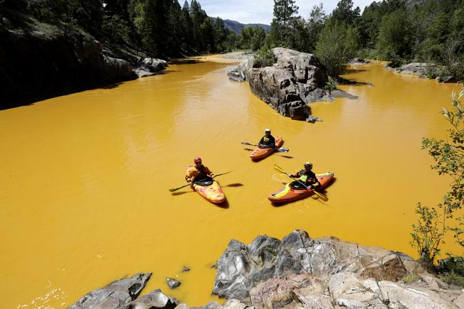 People kayak in the Animas River near Durango, Colo., Thursday, Aug. 6, 2015, in water colored from a mine waste spill. The U.S. Environmental Protection Agency said that a cleanup team was working with heavy equipment Wednesday to secure an entrance to the Gold King Mine. Workers instead released an estimated 1 million gallons of mine waste into Cement Creek, which flows into the Animas River. (Jerry McBride/The Durango Herald via AP) MANDATORY CREDIT